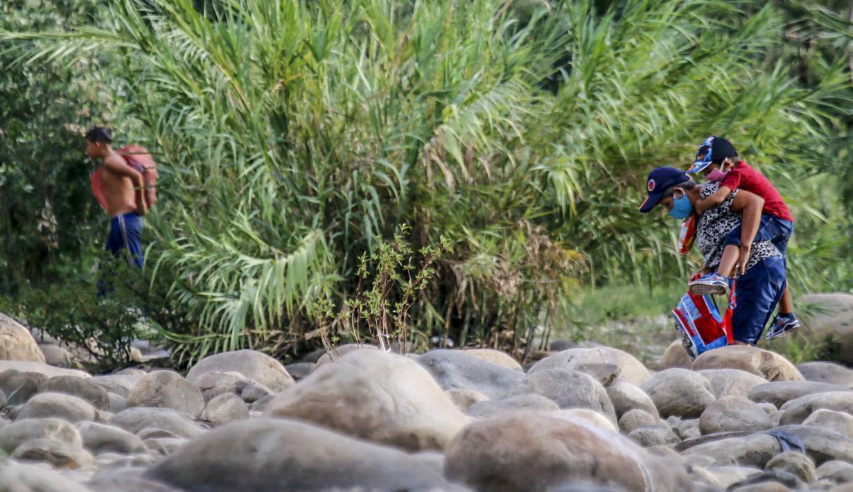 "Warga Venezuela yang mengenakan masker untuk mencegah penyebaran virus corona mencoba masuk ke Kolombia melalui ""trocha"" atau jalur ilegal di perbatasan antara Kolombia dan Venezuela, dekat jembatan internasional Simon Bolivar, di Cucuta, Kolombia (14/10/2020). (AFP/Schneyder Mendoza)"