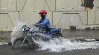 Pengendara motor melewati jalan yang tergenang air saat hujan lebat di New Delhi, India (1/9/2021). Polisi Lalu Lintas Delhi mengeluarkan peringatan yang menginformasikan bahwa ada penghalang lalu lintas di Subway Pasar Azad menuju Pratap Nagar karena genangan air. (AFP/Prakash Singh)