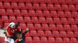 Pemain RB Leipzig, Christopher Nkunku, duel udara dengan pemain Mainz 05, Jeffrey Bruma, di Mainz, Minggu (24/5/2020). RB Leipzig menang dengan skor 5-0 atas Mainz 05. (AP/Kai Pfaffenbach)