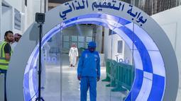 Pekerja melewati gerbang sterilisasi mandiri yang didirikan di pintu masuk Ka'bah dan Masjidil Haram sebagai langkah pencegahan di tengah pandemi COVID-19 di Mekkah pada 8 Mei 2020. Gerbang ini dilengkapi teknologi canggih berupa kamera thermal untuk mendeteksi suhu dari jarak 6 meter. (STR / AFP)