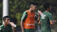 Pemain Timnas Indonesia U-22, Rifal Lastori, melepas dahaga saat latihan di Lapangan ABC Senayan, Jakarta, Senin (7/1). Latihan ini merupakan persiapan jelang Piala AFF U-22. (Bola.com/Vitalis Yogi Trisna)