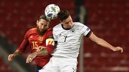 Gelandang Jerman, Julian Draxler, berebut bola dengan bek Spanyol, Sergio Ramos, pada laga Nation League di Mercedes-Benz Arena, Berlin, Jumat (4/9/2020) dini hari WIB. Jerman bermain imbang 1-1 atas Spanyol. (AFP/Thomas Kienzle)