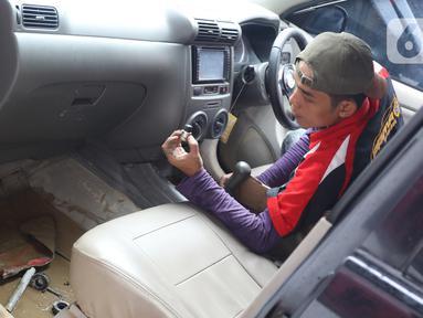 Mekanik mengecek komponen mobil yang terendam banjir di sebuah bengkel di Jakarta, Rabu (8/1/2020). Kerusakan pada mobil yang terendam banjir meliputi interior, kabel dan kelistrikan, serta bagian mesin. (Liputan6.com/Angga Yuniar)