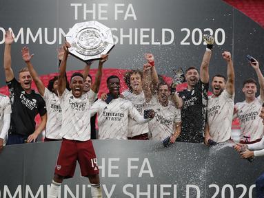 Pemain Arsenal mengangkat trofi Community Shield 2020 usai mengalahkan Liverpool di Stadion Wembley, Sabtu (29/8/2020) malam WIB. Arsenal menang 5-4 atas Liverpool lewat adu penalti. (Andrew Couldridge/Pool via AP)