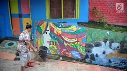 Seorang ibu menyapu sampah di sekitar rumahnya di Kampung Warna Warni Lubuklinggau, Sumatera Selatan, Rabu (10/11). Kampung yang dahulu dikenal sebagai sarang kriminal tersebut kini telah berganti wajah. (Liputan6.com/Immanuel Antonius)