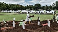 Antrean mobil ambulans terlihat saat proses pemakaman jenazah dengan protokol Covid-19 di TPU Bambu Apus, Jakarta, Kamis (28/1/2021). Pemprov DKI menyiapkan 6 lokasi baru untuk pemakaman jenazah pasien Covid-19 dengan total kapasitas 17.900 petak makam. (merdeka.com/Iqbal S Nugroho)