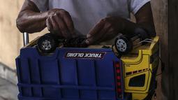 Marsyaad atau biasa dipanggil Pak Umar (79) membuat mobil-mobilan di toko mainan miliknya di Kalibata, Jakarta, Kamis (25/2/2021). Pak Umar yang menjual mainan anak sejak tahun 1974 mengaku tidak terlalu berdampak saat pandemi virus corona COVID-19 berlangsung. (Liputan6.com/Johan Tallo)