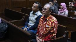 Terdakwa dugaan korupsi pengadaan e-KTP, Irvanto Hendra Pambudi (kiri) dan Made Oka Masagung bersiap menjalani sidang lanjutan di Pengadilan Tipikor, Jakarta, Rabu (21/11). Sidang mendengar nota pembelaan para terdakwa. (Liputan6.com/Helmi Fithriansyah)