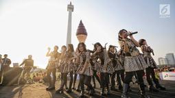 Aksi para personel girlband JKT48 saat tampil dalam puncak Kirab Obor Asian Games 2018 di Monas, Jakarta, Sabtu (18/8). Obor Asian Games 2018 diarak dari Monumen Nasional (Monas) menuju Stadion Utama Gelora Bung Karno (SUGBK). (Liputan6.com/Faizal Fanani)