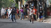 Massa melempar batu ke arah aparat keamanan saat terjadi bentrok di kawasan Slipi, Jakarta Barat, Rabu (22/5/2019). Massa yang terlibat kerusuhan tarpantau sebagian besar masih berusia remaja. (Liputan6.com/Gempur Muhammad Surya)