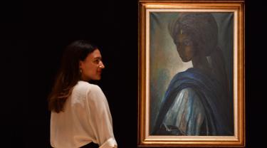 Karyawan rumah lelang Bonhams berpose dekat lukisan seorang putri Nigeria bernama Tutu di London, Inggris pada 7 Februari 2018. Lukisan yang kerap disebut 'Mona Lisa dari Afrika' itu terjual dalam sebuah lelang pada 28 Februari 2018. (BEN STANSALL/AFP)