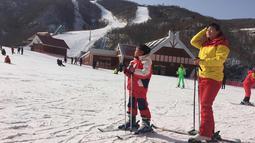 Seorang ibu dan putrinya beristirahat di lereng di resor ski Masik Pass di Korea Utara (28/1). Resor ski ini juga sebagai tempat latihan tim ski Korea Utara dan Korea Selatan menjelang Olimpiade Pyeongchang 2018. (AP Photo / Eric Talmadge)