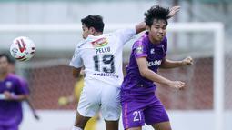 Gelandang Bali United, Rizky Pellu (kiri) berduel udara dengan gelandang Persita Tangerang, Adittia Gigis dalam laga matchday ke-3 Grup D Piala Menpora 2021 di Stadion Maguwoharjo, Sleman, Jumat (2/4/2021). (Bola.com/M Iqbal Ichsan)