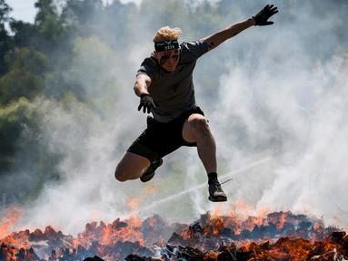 Dua pria menyeberangi rintangan api saat mereka mengikuti kompetisi Tough Viking di Stockholm, Swedia (12/5). Dalam lomba ini peserta harus menempuh jarak 8 km dengan 26 rintangan berat. (AFP/Jonathan Nackstrand)