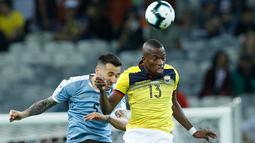 Gelandang timnas Uruguay, Matias Vecino berebut bola dengan pemain timnas Ekuador, Enner Valencia dalam laga pertama Grup C Copa America 2019 di Stadion Mineirao, Brasil, Minggu (16/6/2019). Uruguay berhasil memetik kemenangan besar 4-0 atas Ekuador. (AP/ Victor R. Caivano)