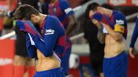 Pemain Barcelona, Lionel Messi dan Gerard Pique, tampak kecewa usai dikalahkan Osasuna pada laga lanjutan La Liga pekan ke-37 di Camp Nou, Jumat (17/7/2020) dini hari WIB. Barcelona kalah 1-2 atas Osasuna. (AFP/Lluis Gene)