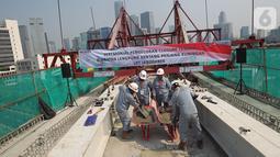 Pekerja melakukan pengecoran akhir jembatan lengkung bentang panjang atau long span pada proyek LRT Jabodebek di Kuningan, Jakarta, Senin (11/11/2019). Long span yang dibangun dengan metode balanced cantilever itu memiliki tipe box girder dengan radius lengkung 115 meter. (Liputan6.com/Angga Yuniar)