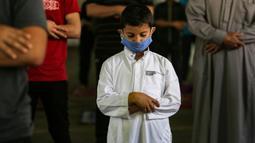Seorang anak Palestina mengenakan masker saat ambil bagian dalam salat zuhur di masjid Al-Abrar di Rafah, selatan Jalur Gaza, Rabu (3/6/2020). Masjid-masjid kembali dibuka bagi jemaah menyusul pelonggaran pembatasan Covid-19 di Jalur Gaza. (Photo by SAID KHATIB / AFP)