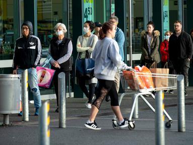 Orang-orang mengantre di luar supermarket ketika Selandia Baru akan beralih ke pembatasan level 3 di Hobsonville, Auckland, Rabu (12/8/2020). Selandia Baru akan memberlakukan lockdown di Auckland setelah ditemukan 4 kasus baru COVID-19 di kota itu. (Dean Purcell/New Zealand Herald via AP)