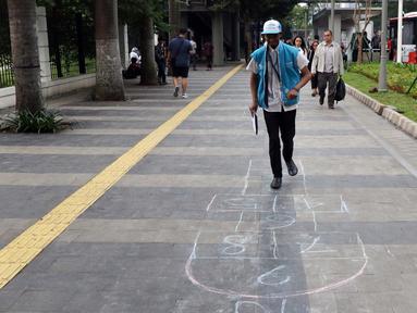 Warga mencoba permainan anak engkle di trotoar sekitar Halte Gelora Bung Karno, Jakarta, Jumat (17/5/2019). Koalisi Pejalan Kaki melakukan eksperimen permainan untuk mengedukasi kegiatan mengembalikan fungsi trotoar lebih dari sekedar ruang berjalan kaki. (Liputan6.com/Helmi Fithriansyah)