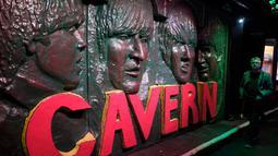 Seorang pria berjalan melewati patung wajah personel The Beatles  di Liverpool, Inggris, (16/8). Kota Liverpool  tiap tahunnya menadapat 105 juta dollar dari para penggemar The beatles dari seluruh dunia yang hadir ke kota ini. (REUTERS/Phil Noble)