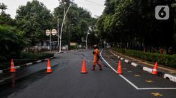 Petugas menutup area kawasan Taman Ayodya, Jalan Bulungan dan Mahakam, Jakarta, Rabu (23/9/2020). Penutupan jalan dilakukan agar masyarakat tidak berkumpul di area tersebut pada waktu malam hari dan menekan angka penularan virus corona COVID-19. (Liputan6.com/Johan Tallo)