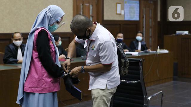 Tersangka dugaan korupsi dan tindak pidana pencucian uang terkait kepengurusan fatwa untuk Djoko Tjandra di Mahkamah Agung, Pinangki Sirna Malasari (kiri) bersiap menjalani sidang di Pengadilan Tipikor Jakarta, Rabu (30/9/2020). Sidang beragenda pembacaan eksepsi. (Liputan6.com/Helmi Fithriansyah)