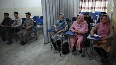 Mahasiswa dan mahasiswi menghadiri kelas yang dipisahkan dengan tirai di sebuah universitas swasta di Kabul, Afghanistan, Selasa (7/9/2021). Universitas di Afghanistan memisahkan pria dan wanita dalam kelas dengan tirai untuk mengikuti keputusan Taliban. (AAMIR QURESHI/AFP)
