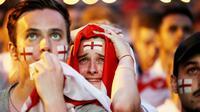 Sejumlah fans tampak kecewa saat timnas Inggris gagal melaju ke final Piala Dunia di Flat Iron Square, london, Rabu (11/7/2018). Kroasia menang 2-1 atas Inggris. (AP/Luca Bruno)
