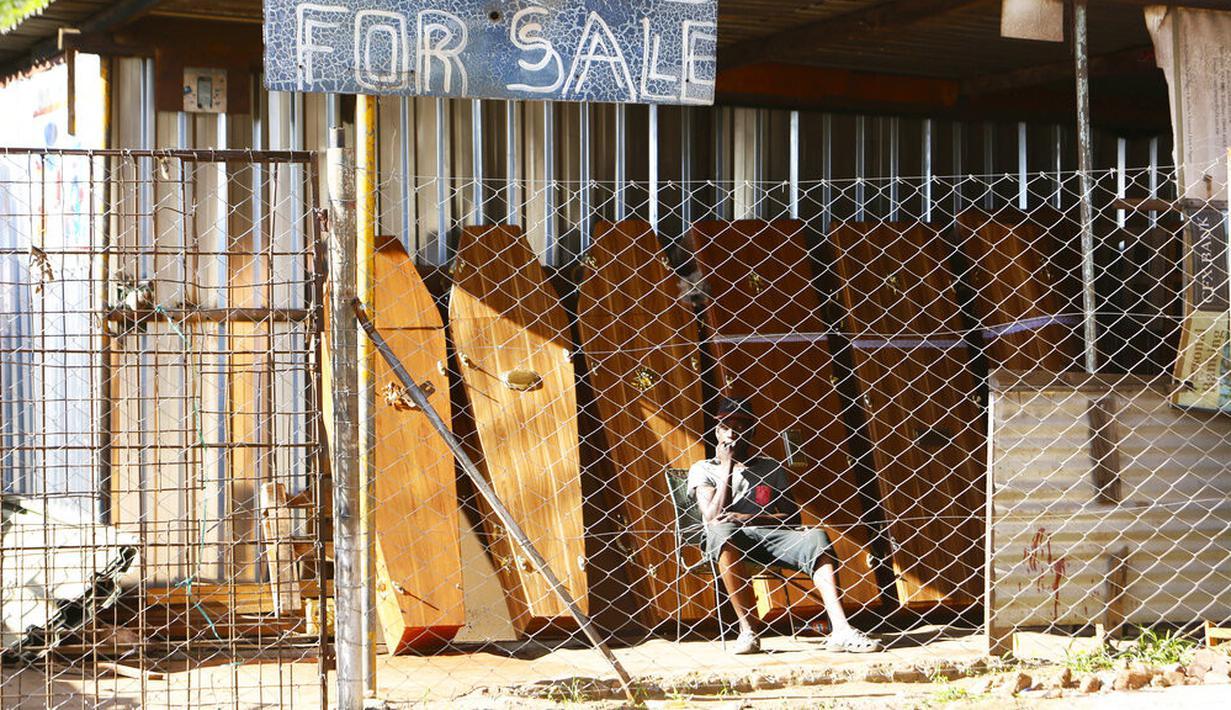 Seorang pekerja perusahaan pembuat peti mati menunggu klien di Harare, Selasa (5/1/2021). Zimbabwe memulai lockdown selama 30 hari dalam upaya untuk mengendalikan lonjakan infeksi COVID-19 yang mengancam petugas kesehatan. (AP Photo/Tsvangirayi Mukwazhi)