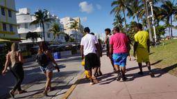 Orang-orang berjalan di sepanjang Ocean Drive di Miami Beach, Florida, Selasa (16/3/2021). Mahasiswa telah tiba di daerah Florida Selatan untuk liburan musim semi. Para pejabat kota prihatin dengan kerumunan liburan musim semi saat pandemi COVID-19 terus berlanjut. (Joe Raedle/Getty Images/AFP)