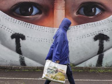 Seorang pria berjalan melewati sebuah lukisan dinding oleh seniman Cosimo Cheone yang didedikasikan untuk perawat rumah sakit Sacco, di Milan, Italia, pada 24 Juli 2020. (AP Photo / Luca Bruno)