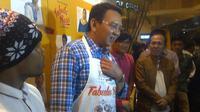 Wakil Gubernur DKI Ahok mengenakan cinderamata berupa celemek bertuliskan Tabula Rasa. (Liputan6.com/Andi Muttya Keteng)