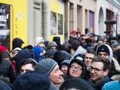 Sejumlah calon pembeli mengantre untuk mendapatkan sepatu Adidas/BVG (Berlin Transport) di luar toko Overkill di Berlin, Jerman, Selasa (16/1). Sepatu tersebut dijual dengan harga 180 Euro atau sekitar Rp 2,95 juta. (AFP PHOTO / Odd ANDERSEN)