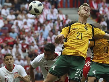 Duel pemain Polandia, Robert Lewandowski dengan pemain Lituania, Justas Lasickas pada laga uji coba di Stadion Narodowy, Warsaw, Polandia, (12/6/2018). Polandia menang 4-0. (AP/Czarek Sokolowski)