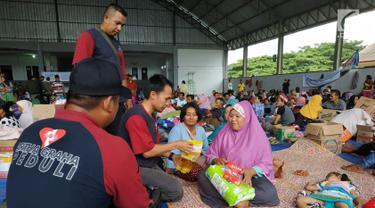 Relawan Artha Graha Peduli (AGP) memberikan bantuan kepada pengungsi imbas tsunami Selat Sunda di Rajabasa, Lampung Selatan, Kamis (27/12). Pulau Sebesi dan Sebuku menjadi  wilayah yang tertutup abu vulkanik Gunung Anak Krakatau. (Liputan6.com/HO/Rini)