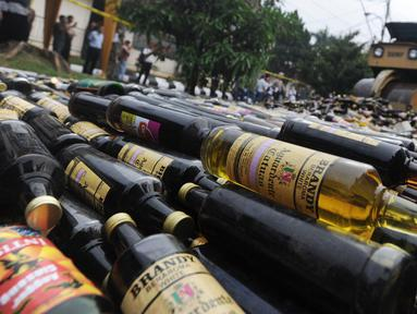 Alat berat menggilas ribuan botol minuman keras  (miras) hasil sitaan polisi di halaman Polres Bogor, Cibinong, Kamis (17/5). Miras yang dimusnahkan lebih dari 32 ribu botol, baik lokal maupun impor dengan beragam merek. (Merdeka.com/Arie Basuki)