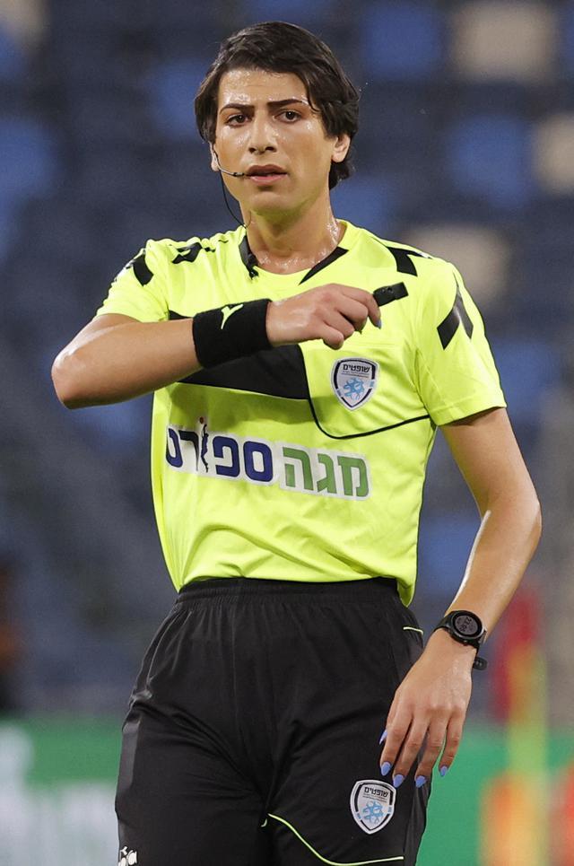 Wasit Sapir Berman memimpin pertandingan Liga Premier Israel antara Hapoel Haifa vs Beitar Jerusalem di kota Haifa, Senin (3/5/2021). Wasit sepak bola transgender pertama Israel turun ke lapangan untuk pertama kalinya sejak tampil di depan umum sebagai seorang wanita pekan lalu. (JACK GUEZ / AFP)