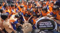 Sejumlah siswa mengumpulkan mainan tradisional othok-othok untuk dikirimkan kepada para korban gempa dan tsunami di Palu dan Donggala, Jumat (12/0).(Liputan6.com/Fajar Abrori)