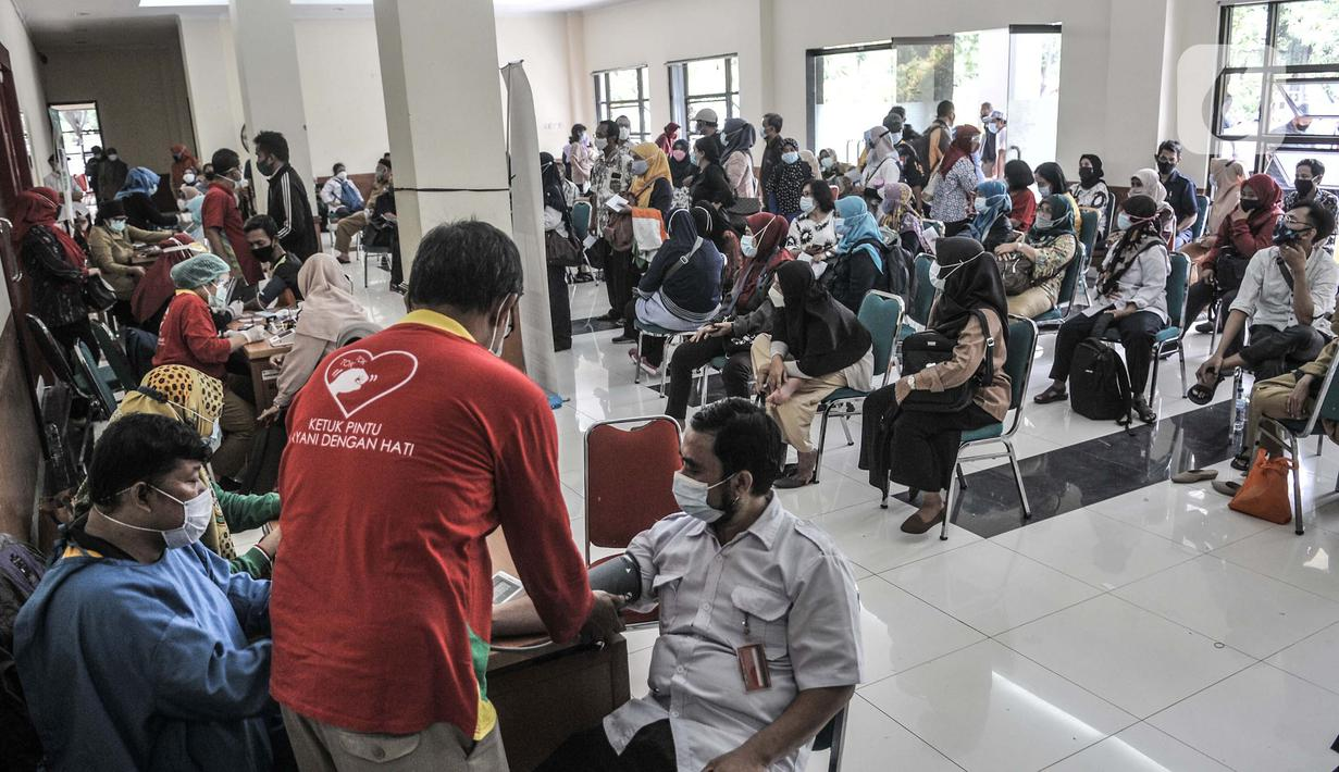 Guru dan staf tenaga pendidik saat antre untuk menerima vaksinasi Covid-19 di GOR Tanjung Priok, Jakarta Utara, Selasa (6/4/2021). Dinas Pendidikan DKI Jakarta menargetkan sebanyak 142.403 guru dan tenaga pendidik menerima vaksinasi Covid-19. (merdeka.com/Iqbal S. Nugroho)