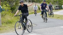 Ibu Negara Jill Biden melambai saat bersepeda bersama Presiden Joe Biden di Pantai Rehoboth, Delaware, Kamis (3/6/2021). Keluarga Biden menghabiskan beberapa hari di Pantai Rehoboth untuk merayakan ulang tahun ibu negara Jill Biden yang ke-70. (AP Photo/Susan Walsh)