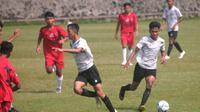 Duel pemain Timnas Indonesia U-16 (jersey putih) melawan tim PPU Kaltim U-15 di lapangan UII, Sleman, Sabtu (22/2/2020). (Bola.com/Vincentius Atmaja)