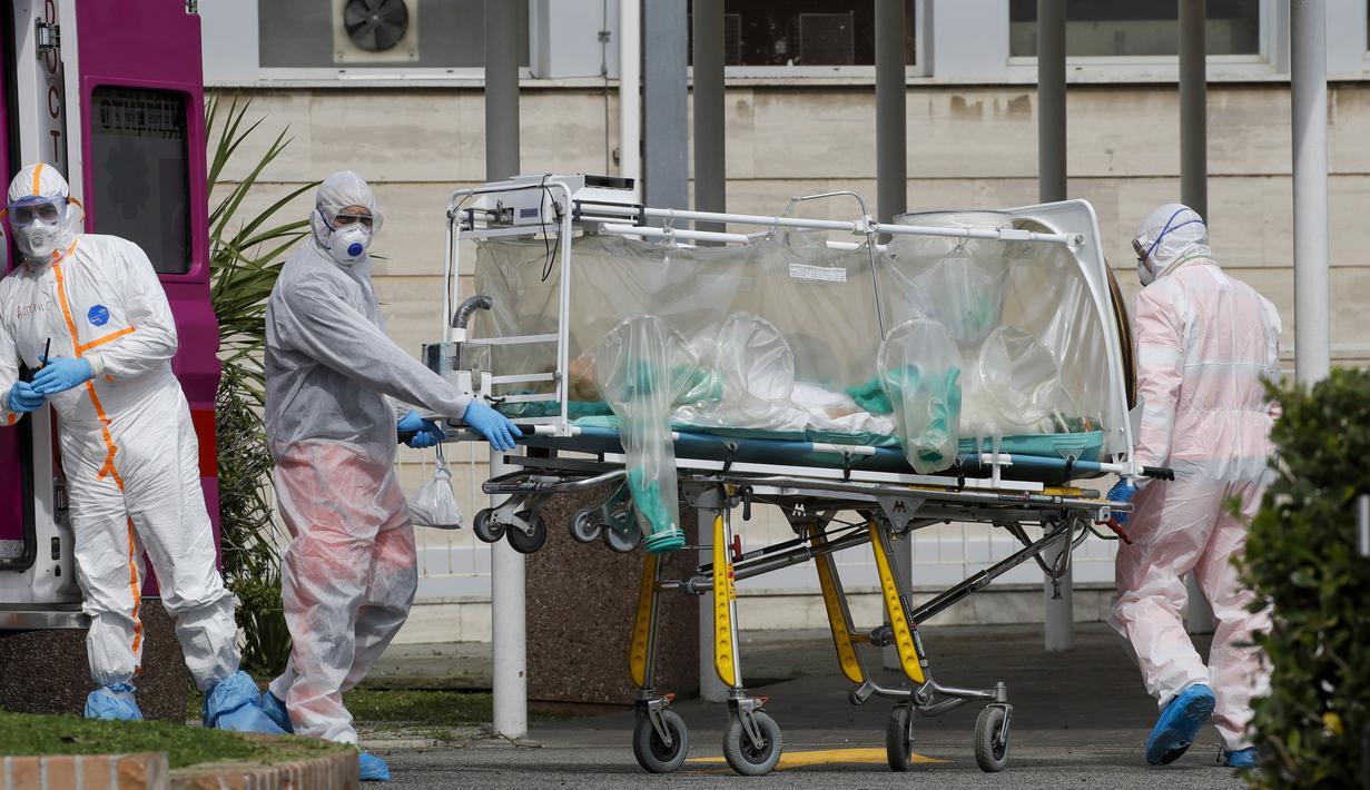 Petugas medis membawa pasien dari ambulans yang tiba di Rumah Sakit Columbus Covid 2 di Roma, Italia, Selasa (17/3/2020). Hingga Jumat (20/3/2020), jumlah kasus virus corona COVID-19 di Italia sudah mencapai 41.035 dengan total kematian sebanyak 3.405 orang. (AP Photo/Alessandra Tarantino)