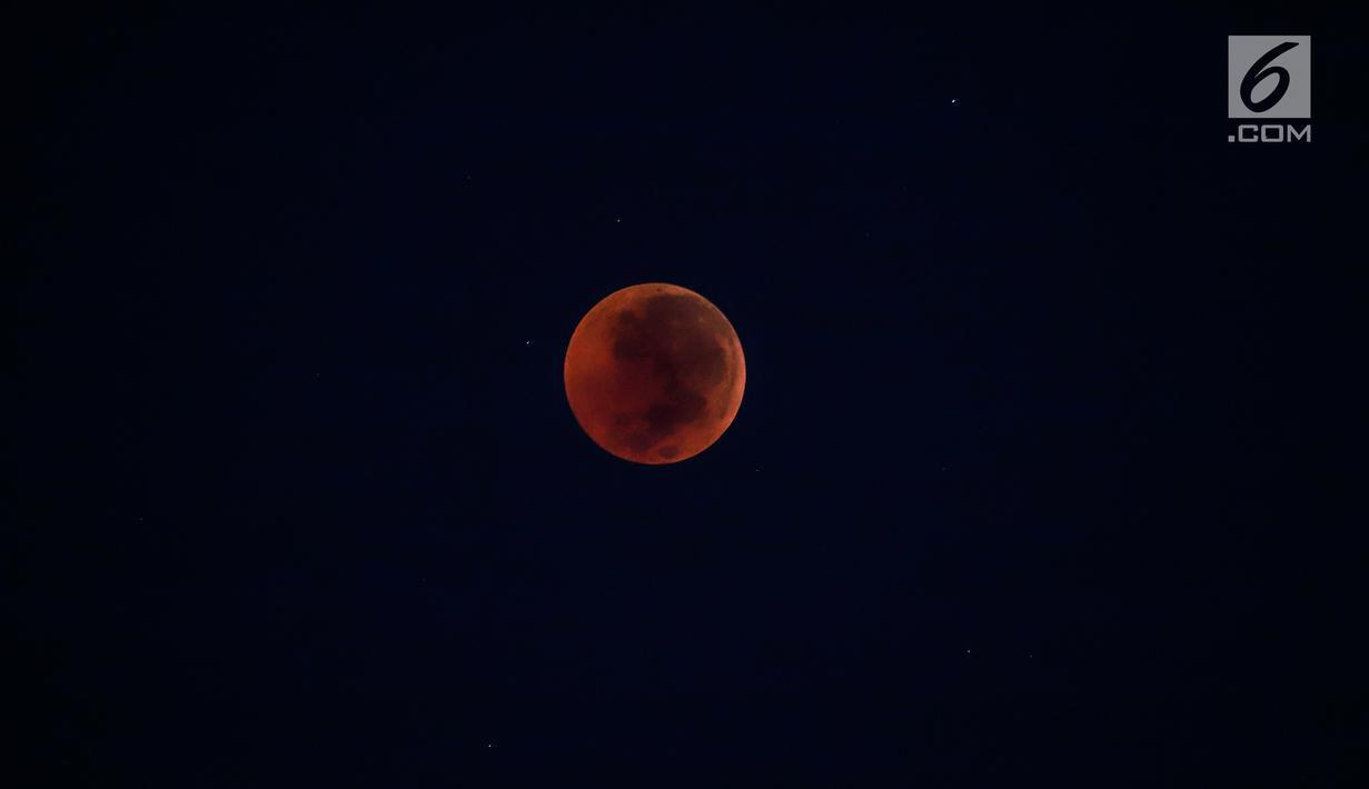 Foto fase gerhana bulan total dI langit kota Jakarta, Sabtu (28/7) dini hari. Gerhana bulan total tahun ini merupakan fenomena langka karena terjadi selama 1 jam 43 menit atau merupakan gerhana terlama yang terjadi di abad ini. (Liputan6.com/Johan Tallo)