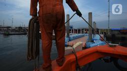 Petugas dari Dinas Lingkungan Hidup DKI Jakarta mengumpulkan sampah di Pelabuhan Kali Adem, Muara Angke, Jakarta, Rabu (6/1/2021). Dalam sehari, sampah pesisir Teluk Jakarta Utara bisa terangkut sekitar 7 kubik sampah plastik yang terbawa dari sungai maupun arus laut. (merdeka.com/Imam Buhori)