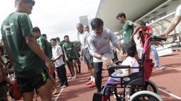 Pelatih Timnas Indonesia U-23, Indra Sjafri, menyapa seorang anak yang datang ke Stadion Madya, Jakarta, Rabu (13/3). Sejumlah anak dari Yayasan Rumah Harapan Indonesia datang menemui Timnas U-23 (Bola.com/Vitalis Yogi Trisna)