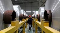 Pekerja memeriksa gulungan aluminium di sebuah pabrik di Zouping di provinsi Shandong bagian timur China (23/11/2019). Zouping adalah salah satu negara terkaya di negeri ini. Kemakmuran ekonominya bergantung pada pengembangan industri aluminium. (AFP Photo/STR)