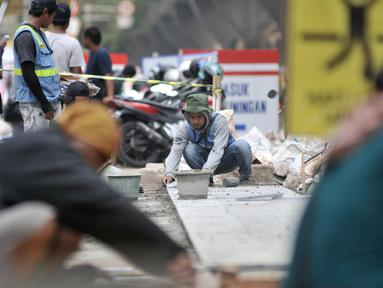 Pekerja menyelesaikan proyek revitalisasi trotoar di kawasan Kuningan, Jakarta, Senin (4/11/2019). Dinas Bina Marga DKI Jakarta menganggarkan biaya proyek revitalisasi trotoar sebesar Rp 1,1 triliun. (merdeka.com/Iqbal Nugroho)