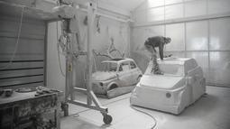 Seniman Italia, Nazareno Biondo saat sedang menyelesaikan replika mobil Fiat 500 berbahan dasar marmer Carrara pahatannya di Cafasse, dekat Turin, Italia, Rabu (16/5). (MARCO BERTORELLO/AFP)