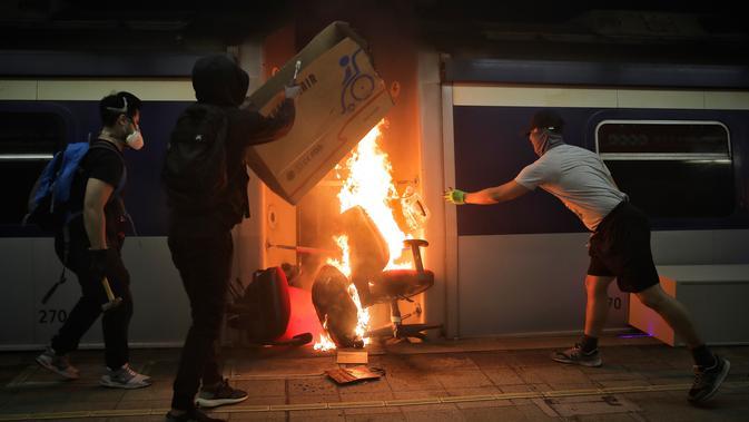 Sejumlah pelajar membakar kereta yang terparkir di Stasiun MTR Chinese University, Hong Kong, Rabu (13/11/2019). Gerakan antipemerintah Hong Kong yang telah berlangsung selama lima bulan bertindak semakin keras. (AP Photo/Kin Cheung)